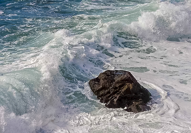 An ocean wave about to break over a rock.