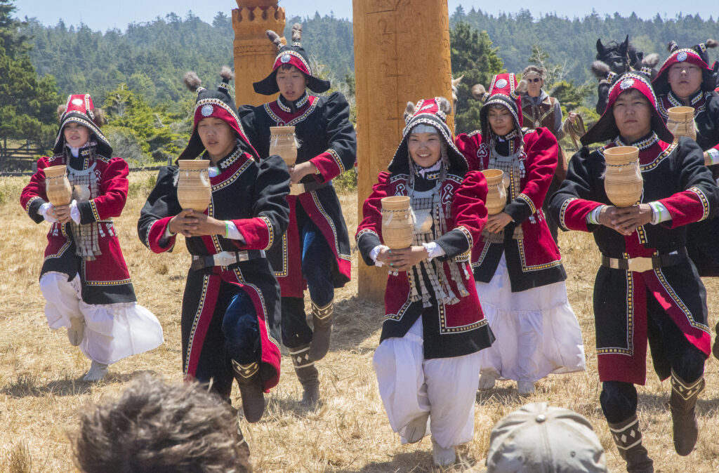 Seven dancers dressed in traditional Siberan attire.